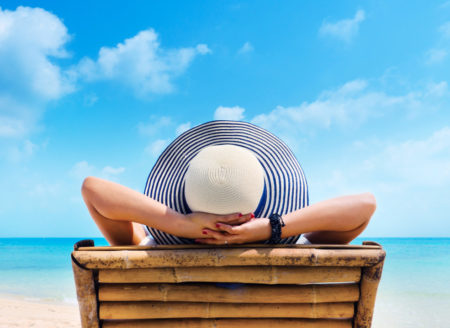 Woman in hat relaxing on beach looking at sea t20 nqd1x7 450x328 1